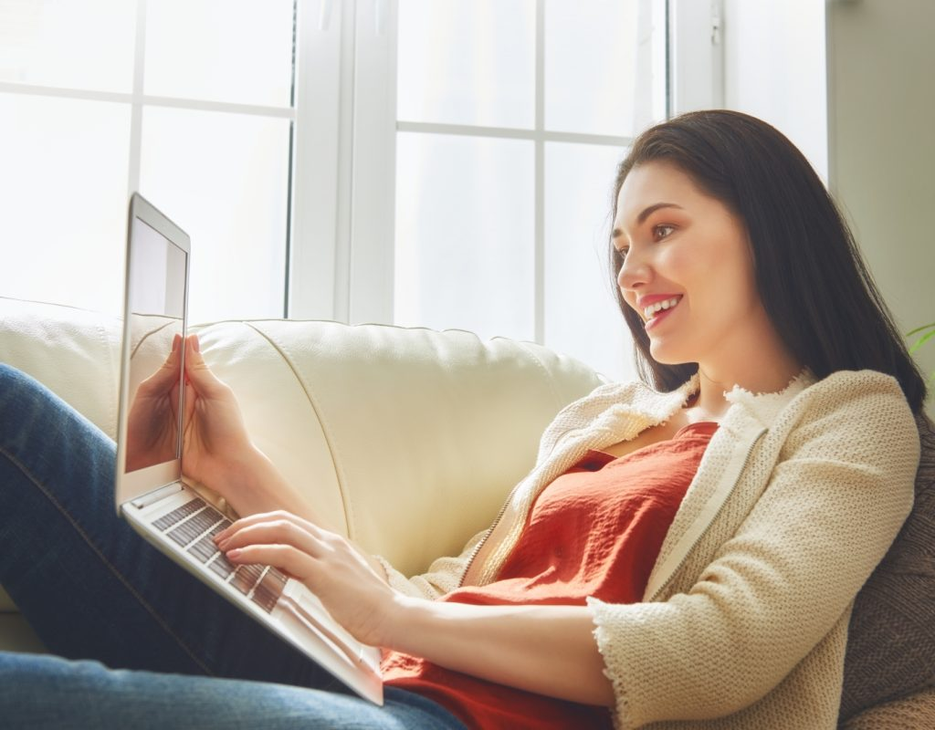 Happy beautiful woman watching videos or enjoying entertainment content on a laptop sitting on the sofa in the house.